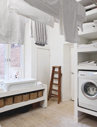 Beautiful utility room. Raising the front-loading appliances and using space below for shelving is a good idea.