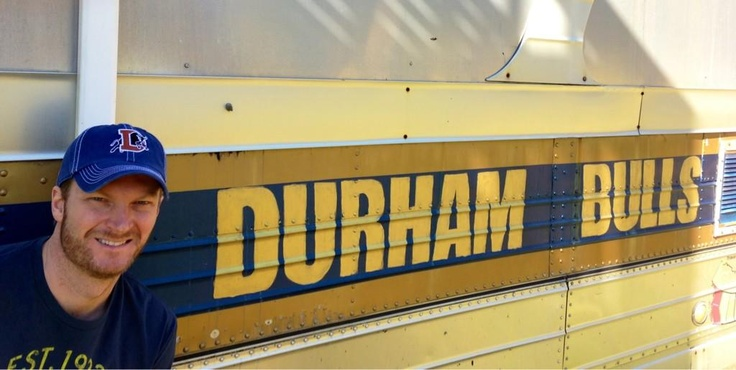 """Dale Earnhardt Jr. showing off his Bulls gear in front of the replica """"Bull Durham"""" bus he owns."""