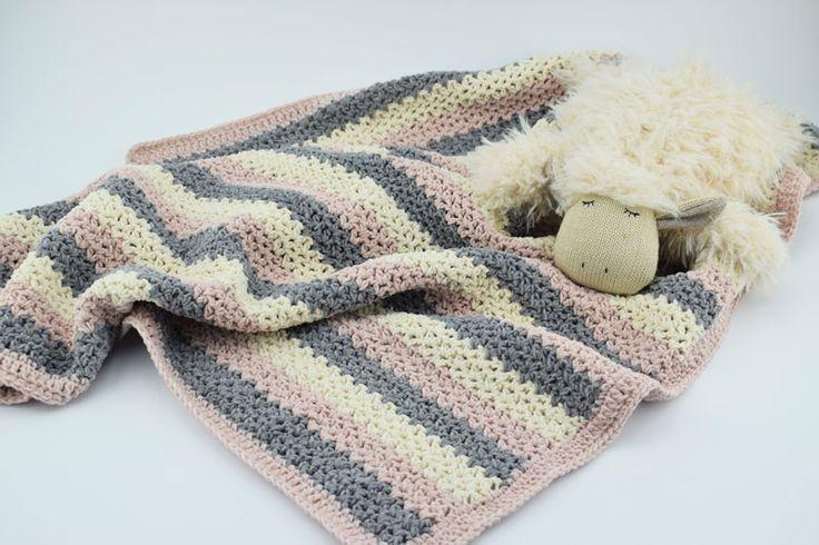 """Hæklet Babytæppe – Velvet/velour Dette tæppe er hæklet i Mayflowers Nye Velour garn – Velvet. Velvet er blødt og let """"fluffy"""" garn i 100 % Bomuld, som findes i 9 skønne farver. Se dem HER Tæppet er hæklet i en et helt enkelt mønster i 3 lækre farver, og måler ca. 85×75 cm. Ønskes tæppet i andre størrelser kan det nemt reguleres med antal af luftmasker, og antal rækker. Det er nærmere beskrevet i opskriften som du finder HER Der er brugt ca. 400 g Velvet fordelt på 3 farver. Du skal brug..."""