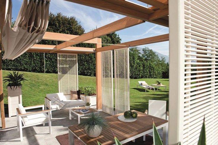 Przesuwane ażurowe parawany zapewniają przyjemny cień i dekorują przestrzeń. Podwieszono je przy belkach, która stanowią jednocześnie konstrukcję do rozpinania płóciennego dachu. Proste meble z drewna i malowanego metalu tworzą minimalistyczne wyposażenie tego tarasu.