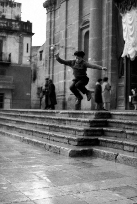 .Ferdinando Scianna - Italy, Sicily, Bagheria:Boy jumping on the stairs of the cathedral. 1962 © Ferdinando Scianna/Magnum Photos.