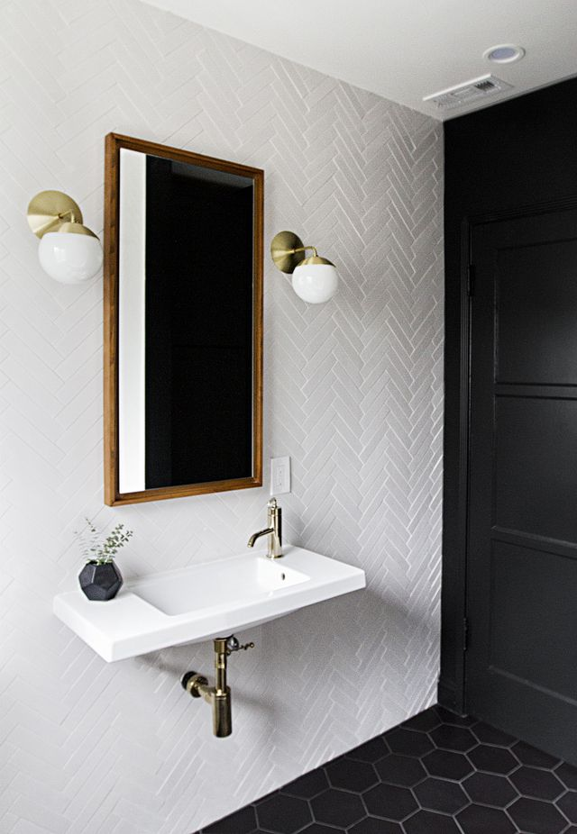Bathroom- black floor tile, white wall tile, brass fixtures