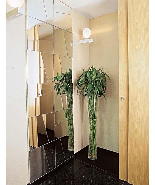Hall de entrada - painel com pedaços de espelho dispostos em inclinações diferentes. Divididas em placas de 40 x 40 cm. O espelho foi colado sobre os quadrados de madeira que compõem o painel de 80 cm x 2,40 m de altura, parafusado na alvenaria. Cada quadrado traz um recorte na diagonal. Além de trazer graça ao espaço e aumentar a sensação de profundidade, esta solução ajudou a alongar o pé-direito, de 2,48 m de altura. Projeto de Valéria Moraes.