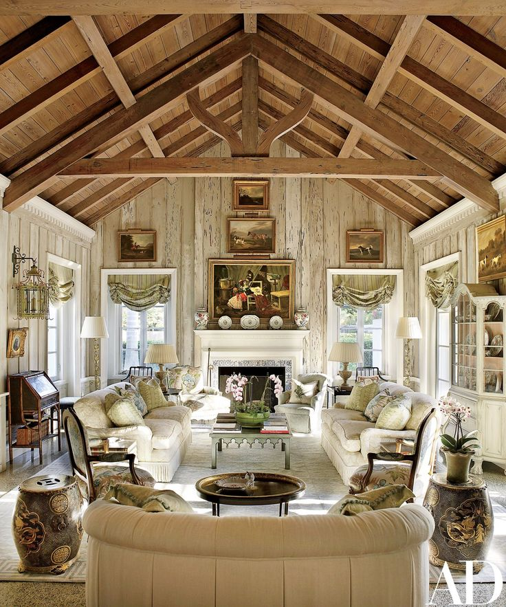 The living room's pecky-cypress paneling was lightened by decorative painter Bob Christian, whose work can also be seen on the tile fireplace surround. The landscape paintings are 19th-century English, the roll-arm sofas are by O. Henry House, and the Louis XV–style armchairs by Edward Ferrell + Lewis Mittman, in the foreground, are upholstered in a Brunschwig & Fils floral; Chinese rice barrels serve as occasional tables.
