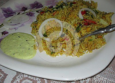 A closeup view of masala rice plate seasoned with curd chutney and onions.
