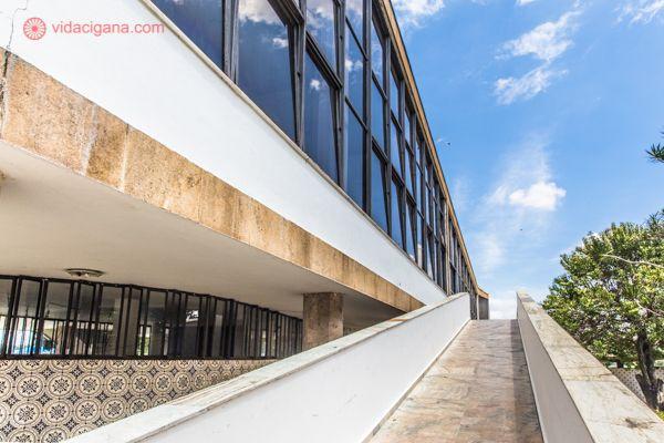 O Iate Tênis Club, em Belo Horizonte, projetado por Oscar Niemeyer. Uma passarela de concreto vai até o topo, chegando em um prédio com enormes janelas de vidro que refletem o céu azul ao fundo, com algumas nuvens brancas.