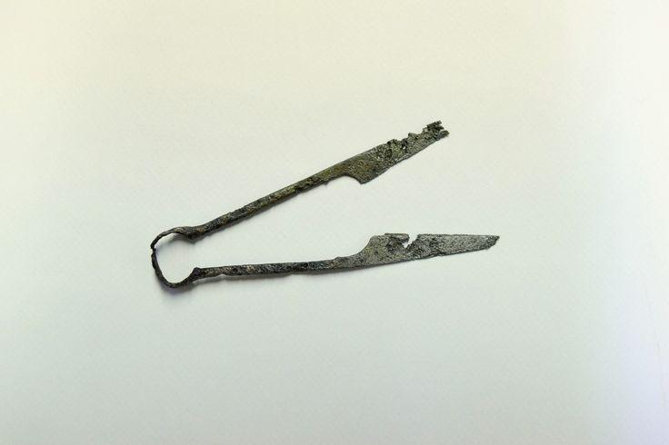 Widoczne na zdjęciu nożyce z około XII wieku – to proste narzędzie tnące, wykonane z jednego żelaznego pręta, odpowiednio zagiętego w kabłąk (stąd określa się je nożycami kabłąkowymi), rozklepanego na końcach w powierzchnie tnące.