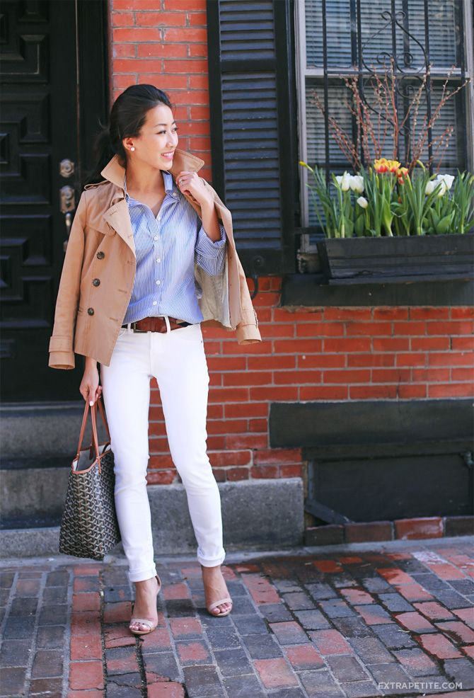 Easy casual spring outfit idea: striped button down shirt, short trench coat, pearls, white jeans, neutral sandals, goyard tote. petites can cuff up too-long jeans