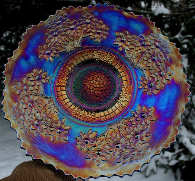 Carnival glass pieces, like this Fenton Orange Tree plate, were given away as prizes at carnivals and movie theaters in the 1910s and '20s. ...