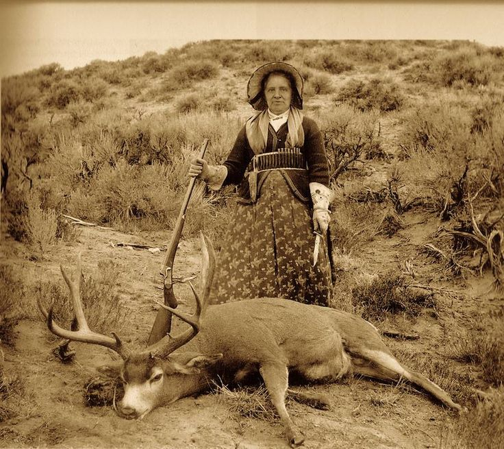 "Augusta ""Gusty"" Wallihan, a noted huntress of the era, with one of her trophy mule deer and her Remington-Hepburn rifle in 1895."