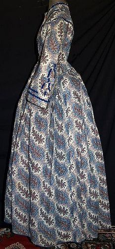 """1860's roller printed gown. Orange, Red & Blue floral sprays on cream wool challis background. Mostly hand sewn. Piped at waist & armscyes, has original brass hooks with handmade round eyeholes. Bodice fully lined with cream linen and openings are lined with brightly printed calico. Skirt has cartridge pleating, hem edged with blue hem protector, has deep right side pocket, skirt lined with cream & brown polished cotton. Bust: 30""""; Waist: 22""""; back length of gown: 57""""."""
