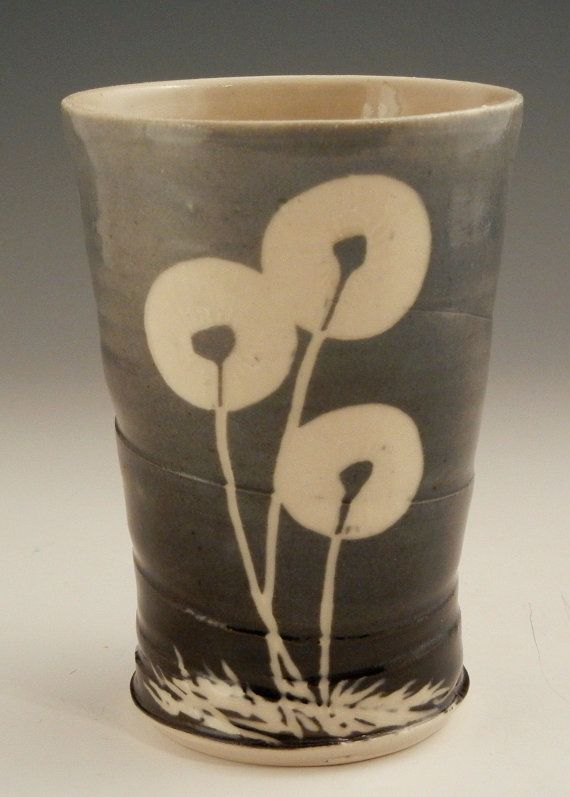 Blue and black ceramic tumbler cup with sgraffito dandelion plant illustration…