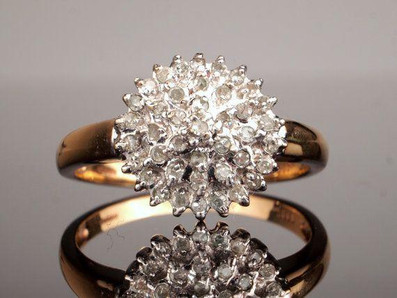 Un atractivo Vintage diamante anillo de compromiso con un grupo de diamantes que suman una cuarta parte de un quilate. Tamaño 8 en Estados Unidos. Vea abajo para las especificaciones.  Este anillo de diamante clúster es típico de la década de 1970 finales a principios de 1980. El anillo de racimo de diamante se puso de moda en los años 70 a través a los años 90 y eran muy popular como los anillos de compromiso. Este anillo de racimo particular tiene tres niveles de diamantes en un anillo que…