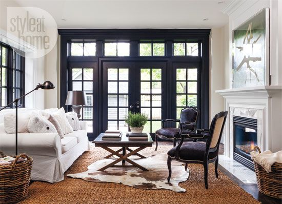 Chic traditional living room: mullioned windows and doors were painted black to make them stand out against the neutral backdrop