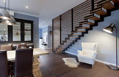 Jednoduché schodiště má zábradlí z vodorovně poskládaných dílců z masivního mořeného jasanového dřeva, které je použito i na nášlapy.