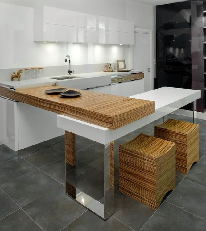 A stunning minimalist kitchen with a mixture of white glossy synthetic countertops and natural wood with a striking woodgrain. The countertops are layered to look as though they weren't originally together. The white and wood of this kitchen is accented by the chrome legs of the island and of the other fixtures.