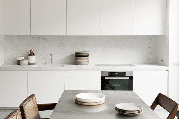 Minimal white kitchen by Nicolas Schuybroek in Brussels with Vincent Van Duysen ceramic bowls and wooden lids