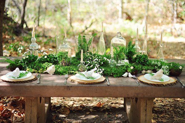 Runner di muschio, felci e piante in vasetto per un tavolo sposi immerso nella natura.