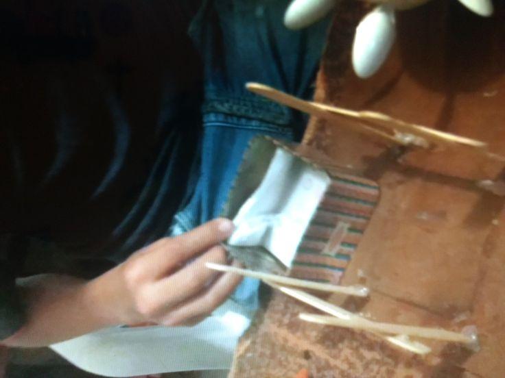 Doblamos la cervilleta y la colocamos en nuestra base metálica y ponemos un poquito de alcohol, esto con el fin de crear una especie mecha. Colocamos la base metálica en el cuadro realizado con los palos de paleta o helado.
