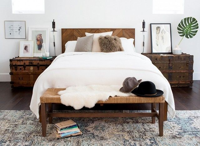 Cozy bedroom with white bedding, wood accents, brown throw pillows, and a bench