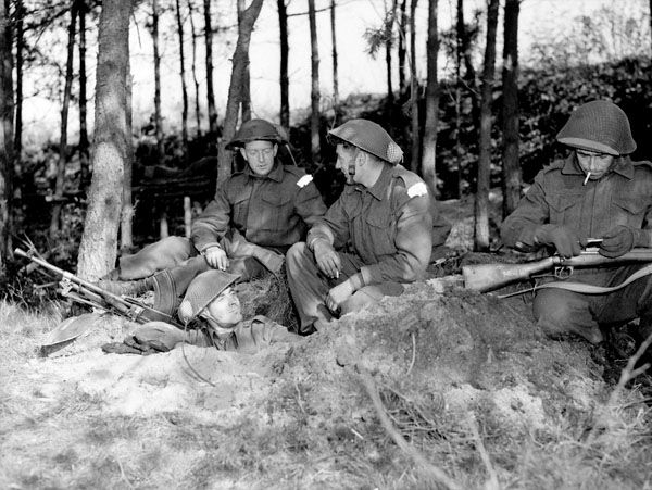 """Infantrymen of """"C"""" Company, The Black Watch (Royal Highland Regiment) of Canada, gathered around a slit trench in the woods near Holten, Netherlands, 8 April 1945. (L-R): Privates E. Cain and Fred Cribley, Lance-Corporal Bill Curtis, Private Gord Bussey."""
