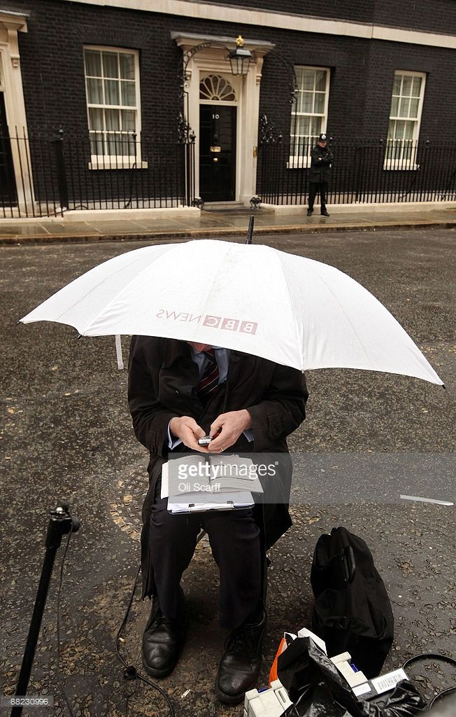 A BBC reporter texts on his phone under an umbrella outside Number 10 Downing Street on June 5, 2009 in London, England. Prime Minister Gordon Brown is today carrying out a reshuffle of his Cabinet following the high-profile resignations of several Cabinet ministers.