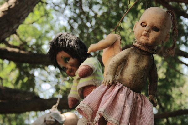 An island filled with hundreds of hanging, decomposing, decapitated dolls.