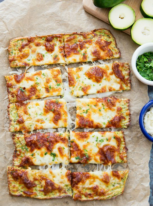 "Zucchini crust ""bread"" is topped with cheese for a low-carb alternative to traditional breadsticks. Do you remember my cauliflower breadsticks and zucchini pizza? Well this recipe combines them both. It has a thin, chewy, pizza-like crust, topped with bubbly, melted cheese. It's super delicious and you get some extra vegetables into your body as well. I've …"