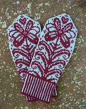 Feminine floral mittens knit in the round from the cuff up in Stranded Knitting. Featuring a two color rib, different patterns on the front and palm of mittens along with a stripe defining the edges of mitten along with the thumb.