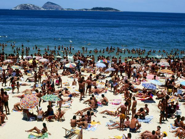 Copacabana Beach - Families, swimmers, and sunbathers crowd Copacabana Beach in Rio de Janeiro. With its crescent of sand, hotels, restaurants, bars, and shops, Copacabana might well be the most famous beach in the world.