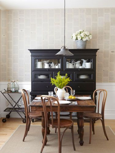 Adding Age - The owner of this Washington home covered the wall in book pages adhered with diluted craft glue she had on hand. A pendant light from Etsy hangs over antique bistro chairs and a walnut table, while a jute rug from Ikea adds definition.