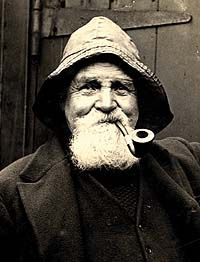 Shows a black and white photograph of a white-bearded fisherman wearing a sowester and smoking a pipe.
