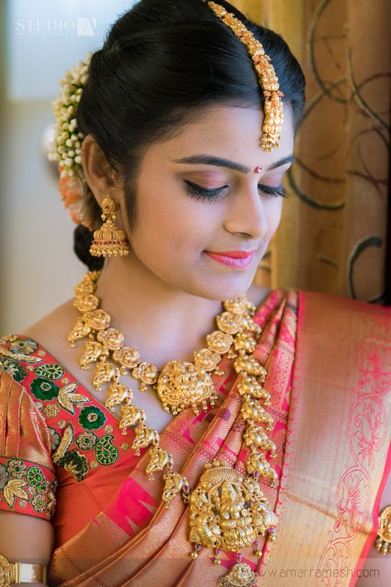 Fabulous distinct contrast pink blouse is decked out with contrast stone thilagam design and stone border jardhosi is rich complimentary for the bride saree.