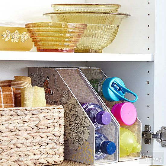 Originally intended to catalog cooking magazines, these flowery organizers turn upside down to neatly store assorted water bottles, which would otherwise take up too much cabinet space. Match the patterned organizers to the hue of your kitchen's linens and wall color./