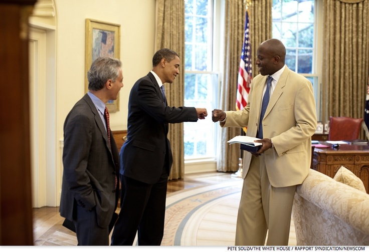 Former Personal Aide Reggie Love receiving a fist bump in the Oval Office of the White House. Then Chief of Staff Rahm Emanuel is seen on the left, June 16, 2009.