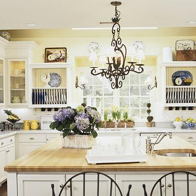 Country Kitchen. Love the soft yellow and clean white look. Not a fan of those iron chairs, but by God I will live and die in a country kitchen one day.