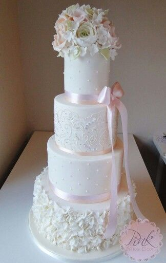 Wedding Cake with ruffles, pearls, piped dress detailing, bows, peach and blush sugar flowers