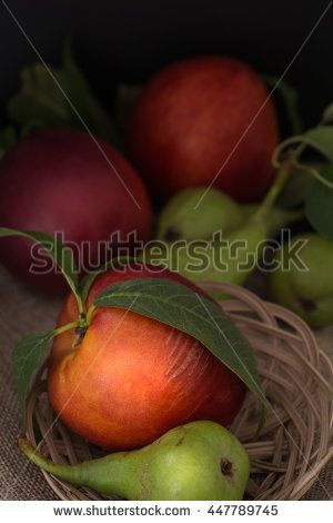 Organic pears and peaches on cloth closeup background, dark photography.