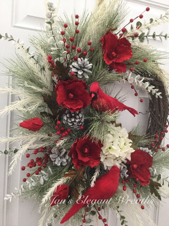 I would classify this exquisite Christmas wreath to be in the glamour category. The grapevine wreath base is covered about 2/3 of the way around with icy pine branches. 4 bright red glittered velvet poppies, along with a cream colored iced hydrangea decorate the light green branches. Making it even fuller yet are cream colored pine branches and lots of iced eucalyptus branches. Large snowy pinecones and bright red berries add color bringing it all together. Last, but not least, 2 large (...