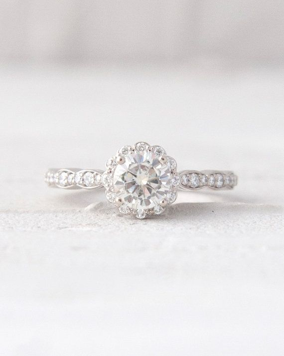 This a stunning vintage inspired ring with a delicate scallop detailing and accent diamonds radiating from the center stone, a round Forever