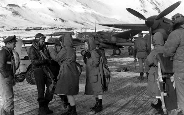 Navy nurses are greeted by U.S. Army Air Corps officers as the women arrive at an air field on Attu Island in the Aleutians during World War II.