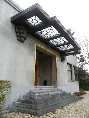 La villa Empain sur l'avenue Roosevelt de Bruxelles, dans le bois de la Cambre. la porte en fer forgé coiffée d'un imposant auvent soutenu visuellement par deux appliques lumineuses en console.