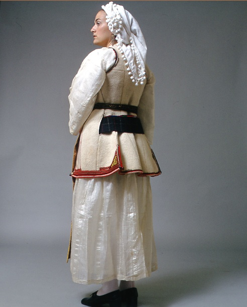"""Central Greece: Back of Desfina costume """"Female Desfina costume from the Phokis region as it developed in the early 20th c. in a very simple composition. It has two chemises one on top of the other, a short sleeveless white coat kept in position with a characteristic of the region dark blue striped belt, as well as the narrow long apron with yellow or gold cord embroidery. Last but not least a white butter muslin kerchief ornamented with small pompoms or 'chenille' fringe."""""""