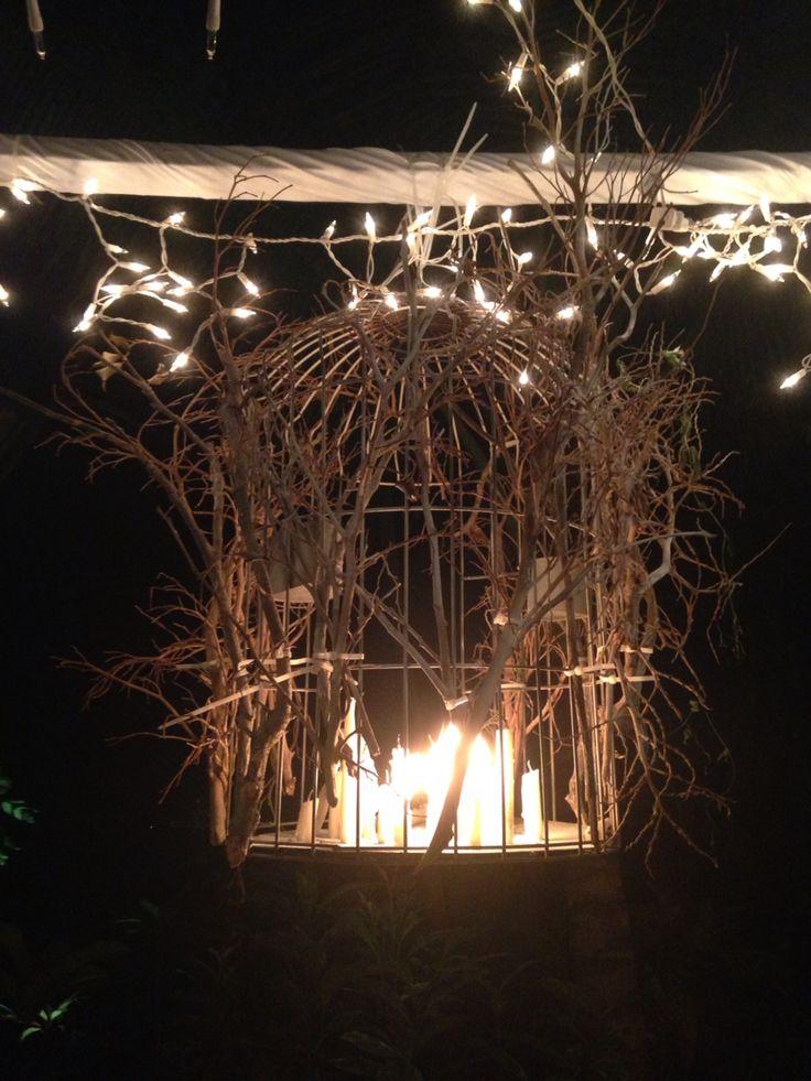 Decora una jaula vieja con ramas secas y naturaleza muerta y llénala de velas de diferentes tamaños. La jaula está colgada sobre una percha forrada con tela y luces para una cena al exterior.