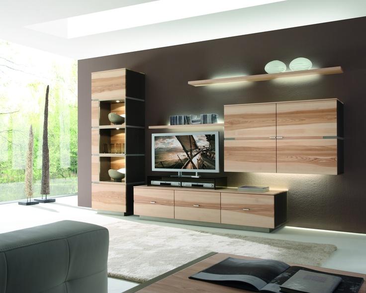 Einen ganz besonderen Charme von Harmonie und Ausgeglichenheit verleiht diesem Wohnraum seine spezielle Atmosphäre. Die rotbraune Wandgestaltung in Verbindung mit indirekten Lichtquellen erzeugt Wärme und Geborgenheit und steht im Kontrast zur weißen Deckenfarbe. Ein flauschiger Läufer lässt noch mehr Gemütlichkeit aufkommen und große Tageslichtfenster erzeugen ein natürliches Flair. Die hellen Holzmöbel, kombiniert mit verschiedenen Materialien, lassen den Raum elegant und modern wirken.