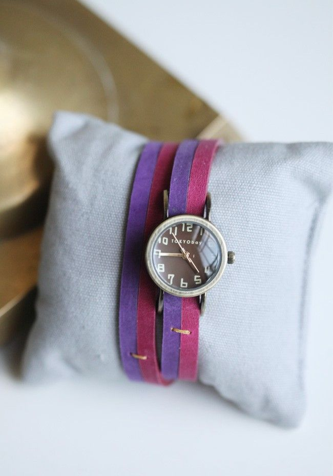 Leela Wrap Watch By Tokyo Bay  99.99 at shopruche.com. This casually chic watch, features a wrapped leather band in a pink and purple palette. Finished with a brown face, subtle mustard accents and gold colored hardware.  Leather band , 16'' L x .4'' W , Clock approx. .75''