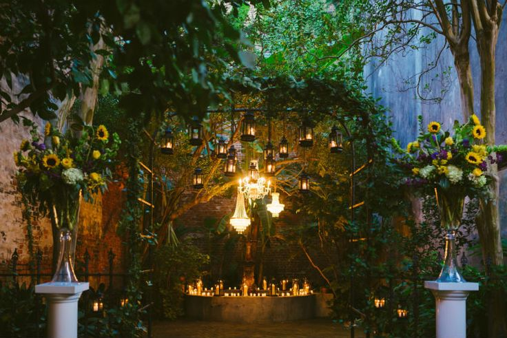 Love the idea of chandeliers and lanterns mixed mixed together with plant and candle backdrop