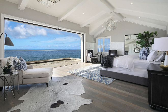 White Cape Cod Beach House. Lots of pictures of exterior and interior. Bedroom folding doors -Beach house master bedroom with folding patio doors. #Bedroom #foldingdoors #Patiofoldingdoors Brandon Architects, Inc