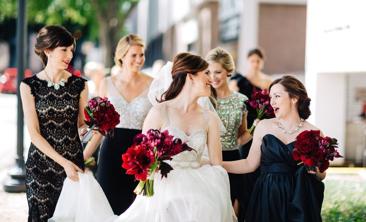 on the way to her uptown wedding, the bride and her bridesmaids carry their bouquets of red amaryllis, burgundy mini calla lily, black parrot tulips, burgundy astilbe, deep red roses, chocolate cymbidium orchids, pink mink protea, burgundy dahlias and begonia leaf.