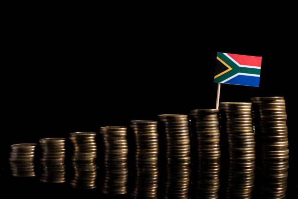 south african flag with lot of coins isolated on black background